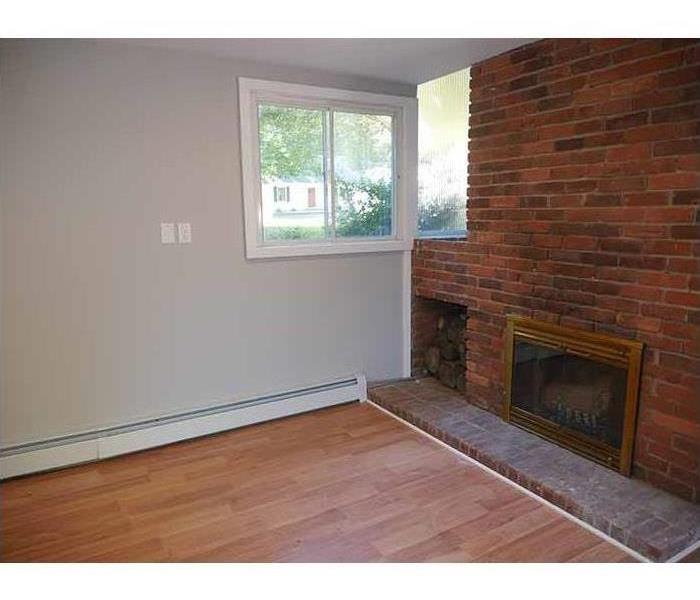 Same fireplace with fresh new hardwood floors and painted walls.