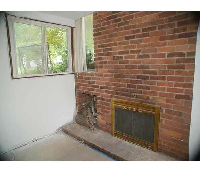 A fireplace with a brick wall, bare floors, and fresh drywall next to the window that caused it all.