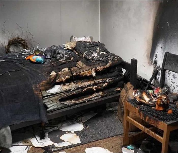 Bedroom with burnt bed, chair, and belongings.
