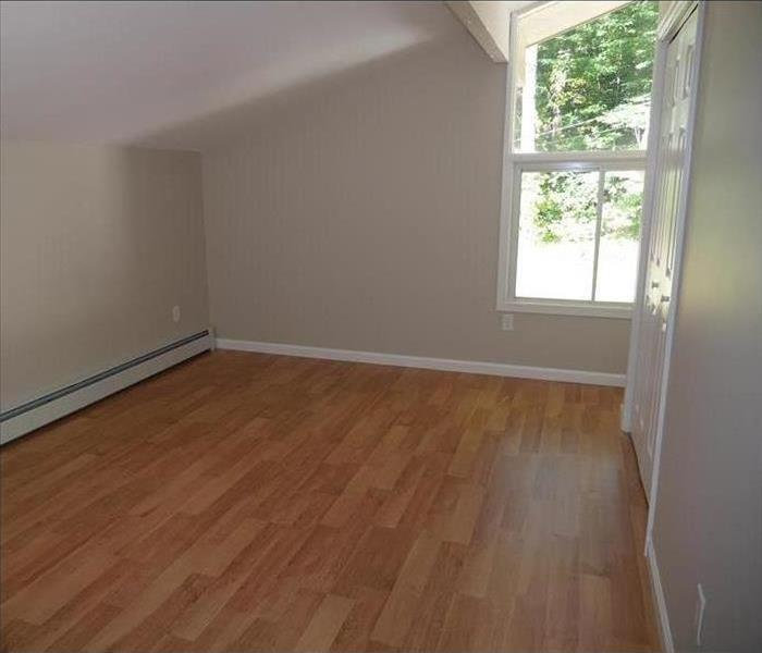 A brand new looking room with fresh walls and hardwood floors.