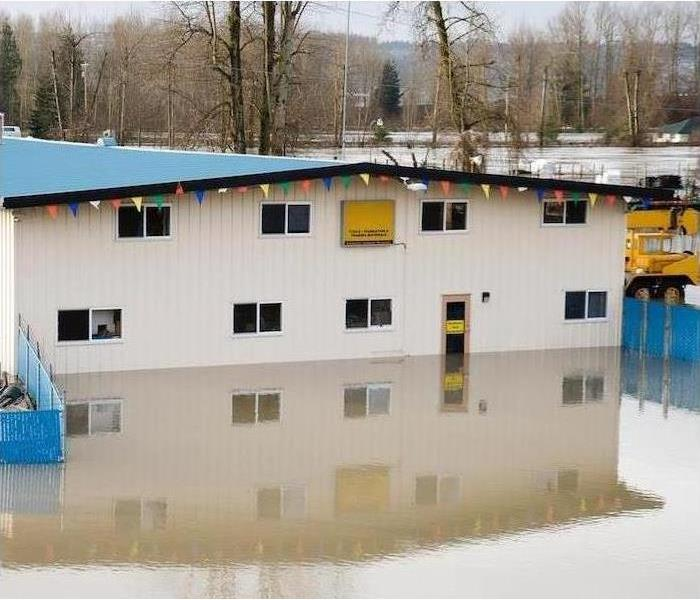 An industrial building is surrounded by flood water