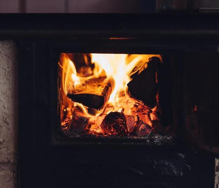 A fire burns inside a wood-burning stove.