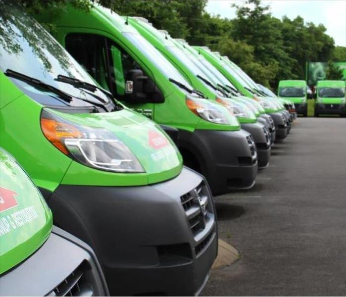 SERVPRO trucks are lined up in a parking lot