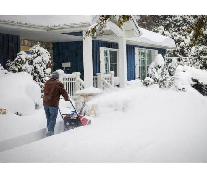 A man clears a sidewalk with a snowblower