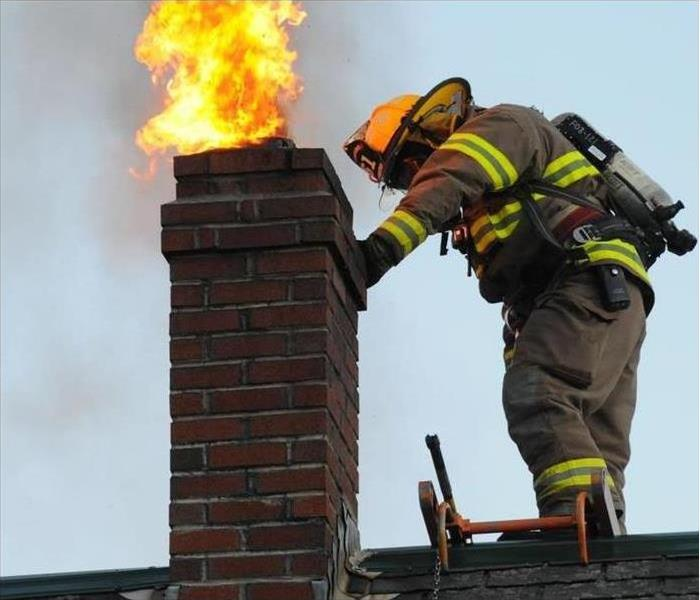 Flames shoot out of a home's chimney.
