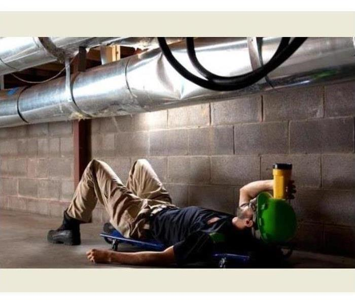 A worker checks ductwork