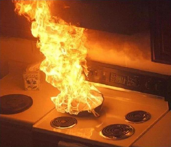 A pan is on fire on a stovetop