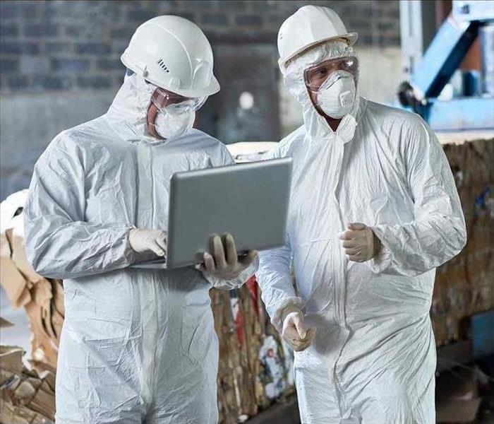 Two workers wear hazmat suits in a warehouse